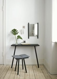 black console table with 2 legs against the wall