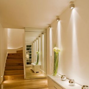 hallway with a mirrored wall and 3 golden wall lamps