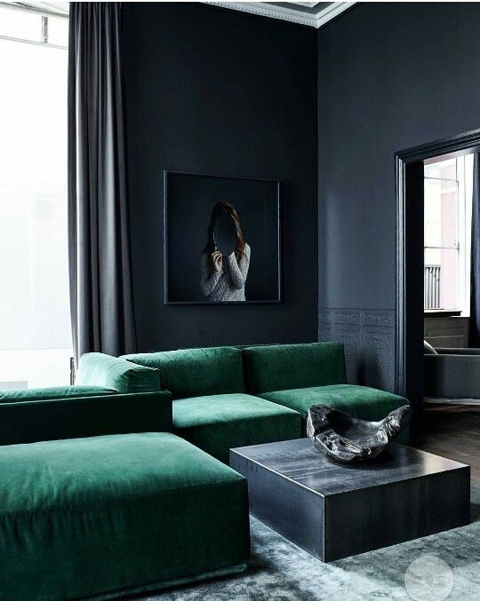 living room with navy blue walls and dark green sofas