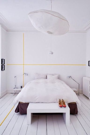 White bedroom with yellow lines on walls and floor