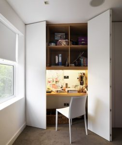 wooden desk integrated in a white cupboard