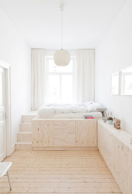 minimalist white bedroom with wooden floor and storage